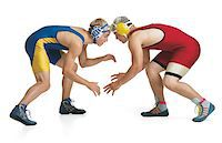 two teenage caucasian male wrestlers from opposing teams face off at the beginning of a match Stock Photo - Premium Royalty-Freenull, Code: 6106-05598458