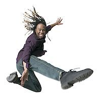 a young adult male in jeans and a purple shirt  jumps and kicks through the air Stock Photo - Premium Royalty-Freenull, Code: 6106-05598582