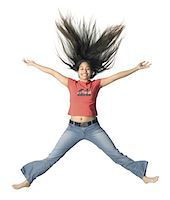 an ethnic female teen in jeans and a red shirt jumps up playfully Stock Photo - Premium Royalty-Freenull, Code: 6106-05598796