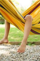 Child's legs dangling from hammock Stock Photo - Premium Royalty-Freenull, Code: 632-05604393