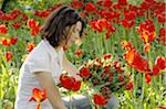 Woman surrounded by red tulips Stock Photo - Premium Royalty-Free, Artist: I Dream Stock, Code: 689-05611158