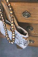 Handbag and necklace hanging at dresser Stock Photo - Premium Royalty-Freenull, Code: 689-05612446