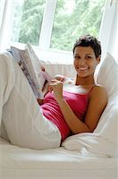 Young woman reading magazine on couch Stock Photo - Premium Royalty-Freenull, Code: 689-05612738