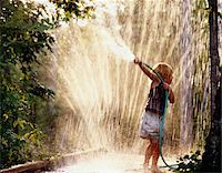 Girl Playing With Water Hose in Garden Sprinkler Stock Photo - Premium Royalty-Freenull, Code: 6106-05624244