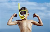 Young Boy Wearing a Snorkel and Flexing His Muscle Stock Photo - Premium Royalty-Freenull, Code: 6106-05625021