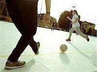 Boys Kicking Soccer Ball Stock Photo - Premium Royalty-Freenull, Code: 6106-05629635