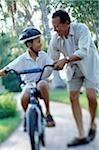Father teaching son (6-8) to ride bicycle (focus on center) Stock Photo - Premium Royalty-Free, Artist: Derek Shapton, Code: 6106-05635122