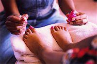 Mother painting daughter's (7-9) toenails, close-up (gel effect) Stock Photo - Premium Royalty-Freenull, Code: 6106-05635406