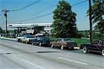 1970s CARS LINED UP AT GAS PUMPS GAS STATION OIL CRISIS OPEC SHORTAGE