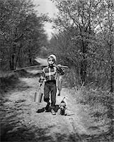 1950s BOY BEAGLE PUPPY WALKING DOWN COUNTRY ROAD WHISTLING CARRYING FISHING POLE PAIL FISH Stock Photo - Premium Rights-Managednull, Code: 846-05645865