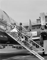 1950s FAMILY FATHER MOTHER DAUGHTER SON BOARDING PROPELLER AIRLINER BY CLIMBING GANGWAY STAIRS AT AIRPORT Stock Photo - Premium Rights-Managednull, Code: 846-05645886