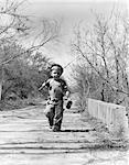 1940s BOY WALKING DOWN COUNTRY ROAD WITH CAN OF WORMS AND FISHING POLE