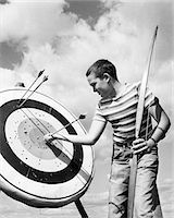 1950s BOY JEANS STRIPED T-SHIRT HOLDING BOW & PULLING ARROW OUT OF TARGET BULL'S-EYE Stock Photo - Premium Rights-Managednull, Code: 846-05645894