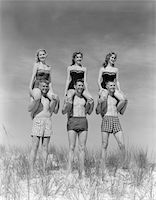 1950s - 1960s THREE COUPLES AT BEACH ON DUNES WITH WOMEN IN IDENTICAL BATHING SUITS SITTING ON MEN'S SHOULDERS Stock Photo - Premium Rights-Managednull, Code: 846-05645933