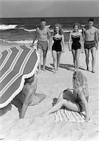 1950s COUPLES IN BATHING SUITS WALKING TOWARDS COUPLE SEATED ON SAND UNDER UMBRELLA Stock Photo - Premium Rights-Managednull, Code: 846-05645934