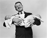1930s PROUD FATHER SMILING PROUDLY HOLDING TWIN BABIES Stock Photo - Premium Rights-Managednull, Code: 846-05645939