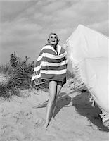 1960s BLOND BATHING BEAUTY WRAPPED IN STRIPED TOWEL WEARING SUNGLASSES STANDING NEXT TO BEACH UMBRELLA Stock Photo - Premium Rights-Managednull, Code: 846-05645952