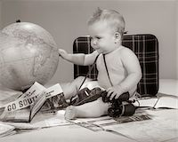 1960s BABY SEATED LOOKING AT GLOBE WITH CAMERA BINOCULARS SUITCASE & TRAVEL BROCHURES Stock Photo - Premium Rights-Managednull, Code: 846-05645964