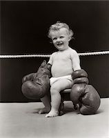 1930s SMILING BABY SEATED ON STOOL IN BOXING RING WEARING OVERSIZED BOXING GLOVES WEARING DIAPER Stock Photo - Premium Rights-Managednull, Code: 846-05645974