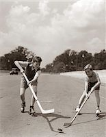 roller skate - 1930s - 1940s 2 BOYS WITH STICKS AND PUCK WEARING ROLLER SKATES PLAYING STREET HOCKEY Stock Photo - Premium Rights-Managednull, Code: 846-05645990