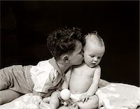people kissing little boys - 1940s CURLY HAIRED BOY TODDLER LEANING AND KISSING CUTE BABY Stock Photo - Premium Rights-Managednull, Code: 846-05645994