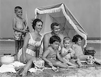 1960s FAMILY OF 6 ON BEACH UNDER UMBRELLA WITH PAILS AND COOLERS Stock Photo - Premium Rights-Managednull, Code: 846-05646005