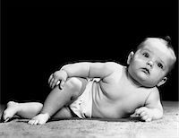 superior - 1940s BABY LAYING ON SIDE PROPPED UP ON ELBOW LEGS CROSSED DISTRACTED EXPRESSION Stock Photo - Premium Rights-Managednull, Code: 846-05646033