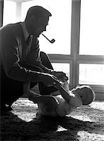 1950s FATHER PIPE IN MOUTH KNEELING DOWN TO PLAY WITH BABY LAYING ON FLOOR SUNLIGHT COMING IN THROUGH WINDOWS Stock Photo - Premium Rights-Managednull, Code: 846-05646094