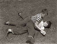 1950s TWO BOYS WEAR TEE SHIRTS BLUE JEANS PLAYING ROUGH FIGHTING WRESTLING ON THE GRASS Stock Photo - Premium Rights-Managednull, Code: 846-05646112