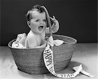 1940s BABY SITTING IN WICKER BASKET WITH HAPPY NEW YEAR BANNER STUDIO INDOOR Stock Photo - Premium Rights-Managednull, Code: 846-05646131