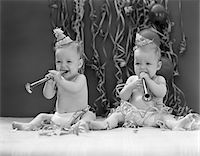 1940s TWIN BABIES WITH PARTY HATS HORNS AND PAPER STREAMERS NEW YEAR CELEBRATION STUDIO Stock Photo - Premium Rights-Managednull, Code: 846-05646139
