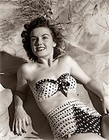 1950s SMILING BRUNETTE WOMAN WEAR POLKA DOT TWO PIECE BATHING SUIT LAYING ON SAND Stock Photo - Premium Rights-Managednull, Code: 846-05646151