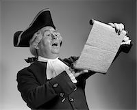 1960s - 1970s MAN IN COLONIAL TOWN CRIER COSTUME READING OFF OF SCROLL Stock Photo - Premium Rights-Managednull, Code: 846-05646177