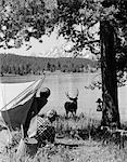 1960s CAMPERS AT GRAND TETON NATIONAL PARK WYOMING SPOTTING BUCK AT LAKESIDE
