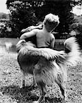 1940s - 1950s - 1960s BACK VIEW OF BOY AND DOG HUGGING