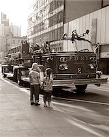 1970s 2 CHILDREN BOY GIRL HOLDING HANDS LOOKING AT FIRE TRUCK PARKED ON STREET NEW YORK CITY Stock Photo - Premium Rights-Managednull, Code: 846-05646324