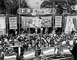 1950s CROWD GATHERED IN FRONT OF STAGE AT COUNTY FAIR FREAK SHOW