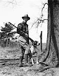 1930s MAN HUNTER WEARING HAT PLAID FLANNEL SHIRT JODHPURS AND BOOTS STANDING HOLDING SHOTGUN WITH POINTER DOG
