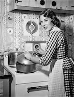 stove - 1950s HOUSEWIFE WEARING CHECKERED DRESS STANDING IN KITCHEN STIRRING POT ON STOVE LOOKING OVER SHOULDER Stock Photo - Premium Rights-Managednull, Code: 846-05646438