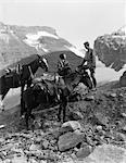 1920s - 1930s COUPLE MAN WOMAN WEARING RIDING GEAR JODHPURS BOOTS SPURS SITTING STANDING ON LARGE ROCK BY TWO HORSES
