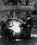 1920s - 1930s THREE MEN HUNTERS SITTING BY STONE FIREPLACE CLEANING POLISHING RIFLE LOADING GUNPOWDER INTO RIFLE
