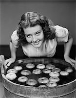 1940s SMILING TEEN GIRL LEANING OVER TUB ABOUT TO BEGIN BOBBING FOR APPLES FLOATING IN THE WATER Stock Photo - Premium Rights-Managednull, Code: 846-05646446
