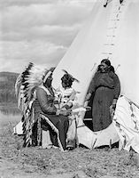 1920s NATIVE AMERICAN INDIAN FAMILY MAN WOMAN CHILD BY TEPEE STONEY SIOUX TRIBE NEAR ALBERTA CANADA Stock Photo - Premium Rights-Managednull, Code: 846-05646472