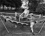 1950s MOM & KIDS SERVING DAD IN HAMMOCK
