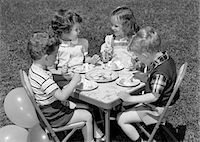 1950s PAIR OF BOYS & GIRLS AT TABLE ON LAWN EATING COOKIES & ICE CREAM FOR BIRTHDAY PARTY WITH BALLOONS AT SIDE Stock Photo - Premium Rights-Managednull, Code: 846-05646531