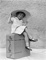 1930s PORTRAIT SMILING LITTLE GIRL SITTING ON SUITCASE WEARING BIG STRAW HAT Stock Photo - Premium Rights-Managednull, Code: 846-05646548