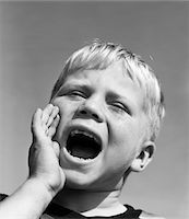 1950s BLOND BOY WITH EYES CLOSED AND HAND CUPPING A WIDE OPEN MOUTH SHOUTING Stock Photo - Premium Rights-Managednull, Code: 846-05646552