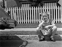1940s GIRL SITTING ON CURB WITH TOOTH TIED TO BACK OF CAR FENDER Stock Photo - Premium Rights-Managednull, Code: 846-05646569