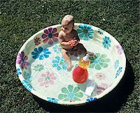 1970s BABY SITTING IN PLASTIC BACKYARD KIDDY POOL VIEWED FROM ABOVE Stock Photo - Premium Rights-Managednull, Code: 846-05646712
