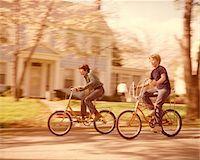 1970s BOYS RIDING BIKES  ON SUBURBAN STREET SPRINGTIME Stock Photo - Premium Rights-Managednull, Code: 846-05646714